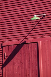Vestiges of a once common past: red barns and green enamel shades on the barn light.