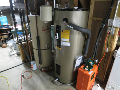 "In the basement the heated glycol enters the orange exchanger where the energy is transferred to an 80-gallon ""pre-heat"" tank; the pump is powered by a small PV-panel."